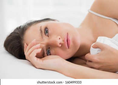 Close-up of a pretty young woman lying in bed