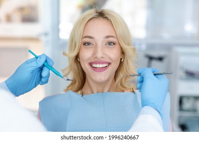 Closeup of pretty young woman showing her white teeth while having checkup at dental clinic, dentist hands in rubber gloves holding dental tools. Female patient getting teeth whitening treatment