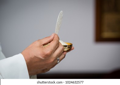 Closeup of priest with communion in the hand. Religious ceremony. Holy communion on a catholic mass. Concept: Free from sins.