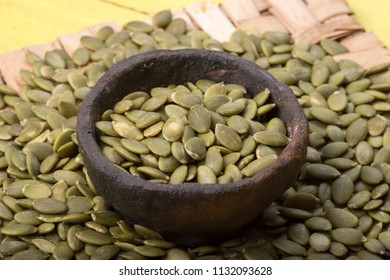 Closeup primitive clay bowl of raw hulled pumpkin seeds among pile of seeds on table