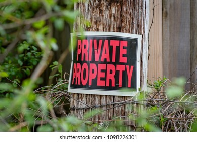 closeup of a private property sign stapled to barbed wire post with thorns