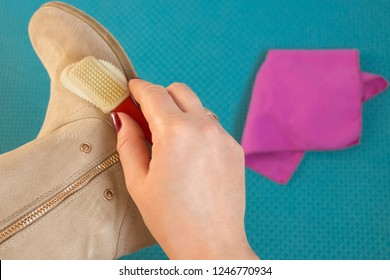 Closeup of the process of caring for suede shoes. A woman cleans suede boots with a special cleansing foam, brush and microfibre cloth. Restoration of suede shoes