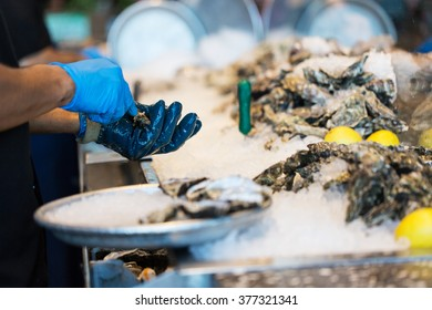 close-up of the process of shucking oysters at the restaurant, shallow DOF on hands