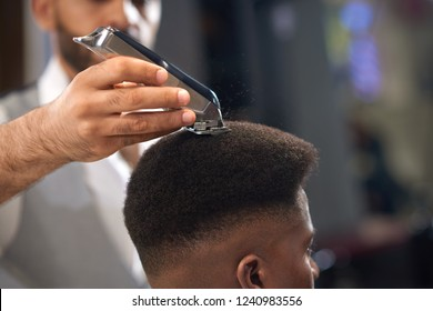Closeup of process of trimming of hair in barber shop. Qualified barber keeping clipper in hands and correcting shape of hair to male client sitting on chair. Concept of haircut and shaving.