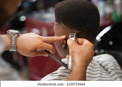 Closeup of process of trimming trendy stripes on head in barber shop. Barber keeping clipper and comb in hands and cutting hair to male sitting on chair. Concept of hairdressing and shaving.