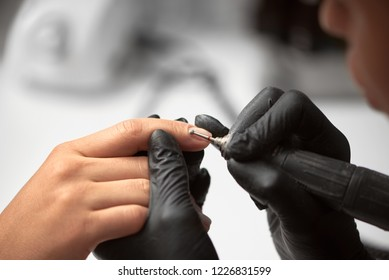 Close-up of professional beautician hands in black gloves working with electric drill file on client fingernails on light blurred background. Fingernails treatment, manicure making in beauty salon.