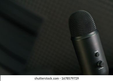 Close-up of professional condenser microphone on a black background.
