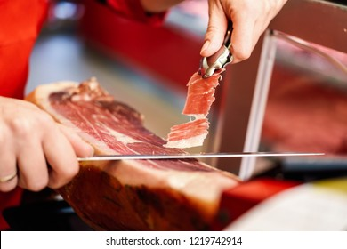 Close-up of professional cutter carving slices from a whole bone-in serrano ham