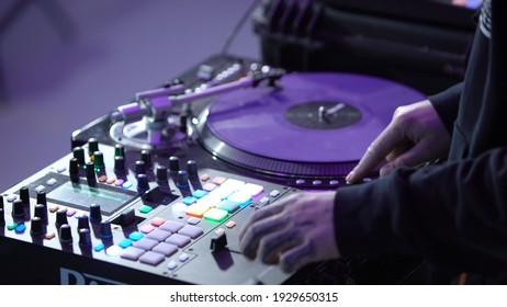 Gros plan sur un DJ professionnel travaillant derrière un mixeur. Art. Cool DJ bascule rapidement les boutons sur le mixeur. DJ professionnel et rapide derrière mixeur
