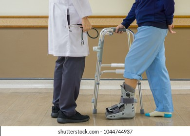 Closeup, Professional doctor holding stethoscope in hand, and look patient is required to use Walker and orthopedic boot to help reduce ankle injury. medical and orthopedic concept.