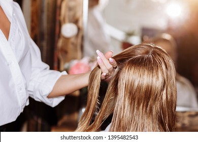 Closeup of professional hairdresser using brush and hairdryer styling long blond hair of her female client. Healthy shiny hair of woman after hair treatment.
