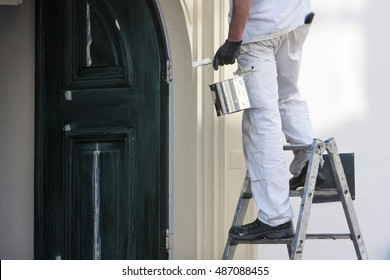 Closeup of a professional house painter with paint and brush