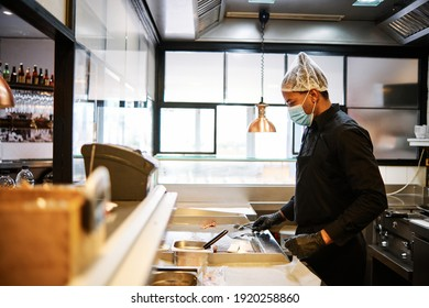 Close-up of professional latin chef man wearing a protective mask and uniform while working at restaurant kitchen.
