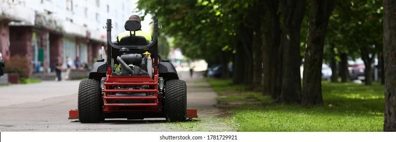 Nahaufnahme des professionellen Rasenmähers mit Arbeiter nach dem Grasschneiden im Stadtpark. Gärtner mit Auto-Rasenmäher auf dem städtischen Platz. Person, die besondere Ausrüstung verwendet