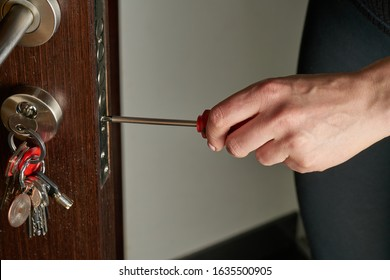 Closeup of a professional locksmith installing or repairing a new deadbolt lock on a house exterior door with the inside internal parts of the lock visible.. - Shutterstock ID 1635500905