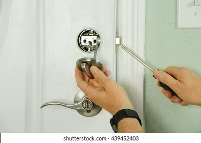 Closeup of a professional locksmith installing or repairing a new deadbolt lock on a house exterior door with the inside internal parts of the lock visible.