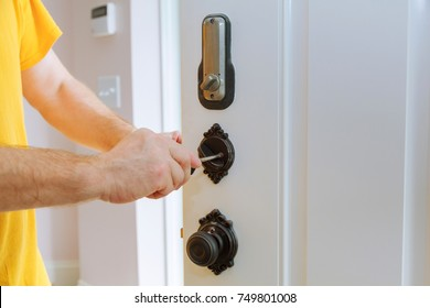 Closeup of a professional locksmith installing or repairing a new deadbolt lock on a house door with the inside internal parts of the lock visible.