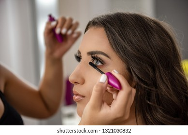 Closeup of professional makeup artist applies mascara to the eyelashes of the model girl. Beautiful woman face with hands of make-up artist, makeup in progress.