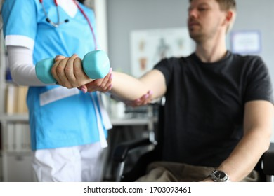 Close-up of professional medical worker helping patient work out arm. Male sitting in wheelchair. Doctor physician in uniform. Modern medicine and disabled people concept