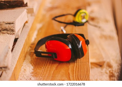 Closeup of professional protective equipment for carpenters and woodworking production workers. Protective headphones, glasses and measuring tape on joiner table. Hearing protectors, joinery workplace