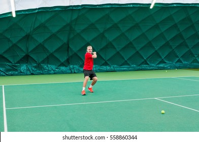 Closeup of professional tennis player dressed in red t-shirt, black shorts and red sport shoes. Man holds tenis racket and playing tennis on court indoor.