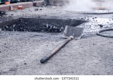 Closeup of professional tools for asphalt repair, road pit, shovel, bitumen against city background. Concept renovation, overhaul of the main street in the city, road construction, industry