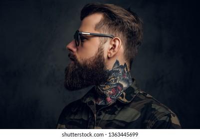 Profil en gros plan d'un homme barbu avec un tatouage au cou dans des lunettes de soleil portant une chemise militaire. Photo de studio sur un mur sombre