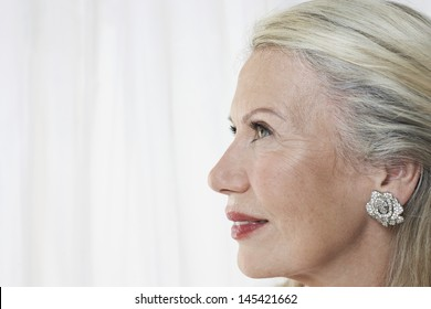 Closeup profile of a beautiful senior woman against white background