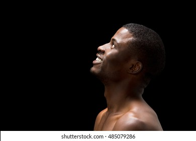 Closeup profile of happy smiling naked black man posing in studio. Handsome Afro-American man with short hair looking in sky or upwards.
