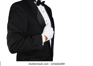 Closeup profile of a man wearing a tuxedo and white gloves holding his lapel. Horizontal format on white. Man is unrecognizable.