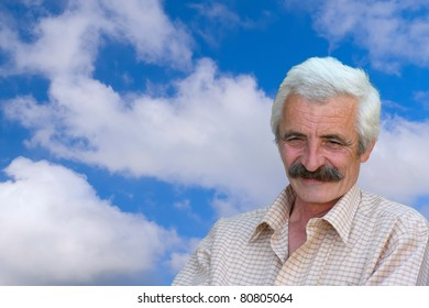 Closeup Profile on a good looking smiling Old Man and blue sky with clouds in the background