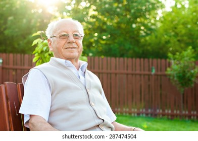 Closeup profile on a smiling old man sitting