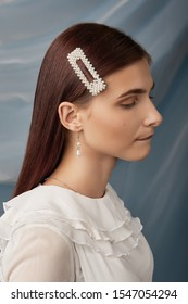 Close-up profile portrait of a dark-haired girl, posing on a blue background. She is wearing white ruffle blouse, pearl earrings and silver chain. Girl has rectangular silver click-clack hair clip on