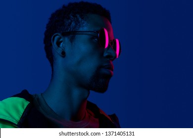 Closeup profile portrait of ethnic black man wearing fashion black sunglasses in blue and pink colors