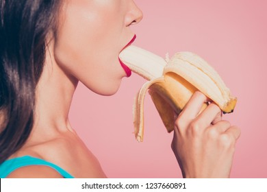Close-up profile side view cropped portrait of nice alluring adorable glamorous charming attractive sweet lovely wavy-haired lady holding biting banana red lips isolated over pink pastel background
