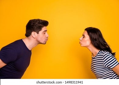 Close-up profile side view portrait of his he her she nice attractive gentle tender affectionate cheerful cheery married spouses kissing closed eyes isolated on bright vivid shine yellow background