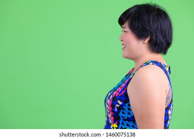 Closeup profile view of young happy overweight Asian woman smiling ready to party