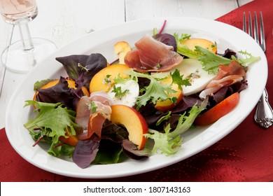 Closeup of Prosciutto peach salad with rresh Mozzarella plate mixed with spring greens. Freash peaches.
