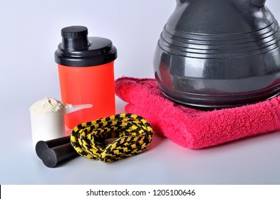 Close-up of protein powder shaker, jump rope, towel and kettlebell - fitness concept, isolated