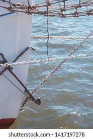 closeup of the prow of a big sailing yacht, with chains and anchor
