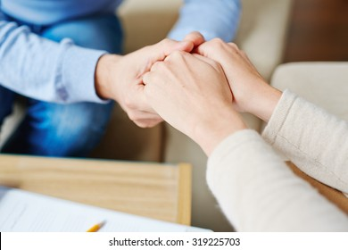 Close-up of psychiatrist hands in those of patient