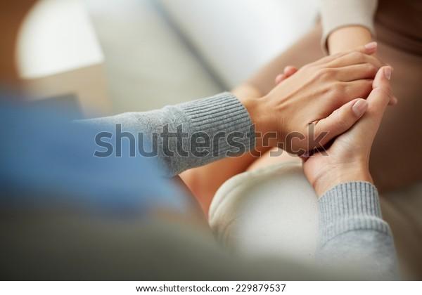 Nahaufnahme von psychiatrischen Händen zusammen, die eine Handfläche ihrer Patientin halten