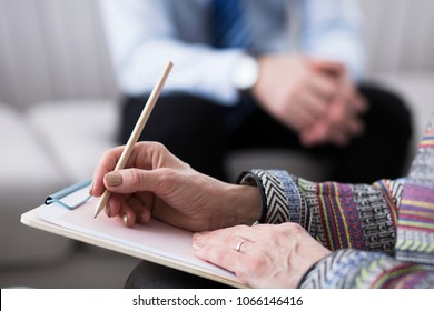 Close-up of psychotherapist writing notes while analyzing her patient