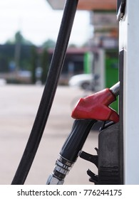 Closeup of pumping gasoline fuel in car at gas station.