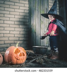 Closeup pumpkin. Little baby witch making a magic potion at Halloween night. Caution! Somewhere near here flying witch mother! Horror. Broom. Halloween costumes for child. Witch.
