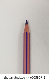 Close-up of purple colored pencil on white background