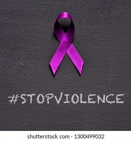 closeup of a purple ribbon, for the awareness about the unacceptability of the violence against women, and the text stop violence on a dark gray background