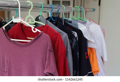 Closeup of purple T-shirt and others hanging on hangers dry in  outdoor sunlight, The simply way of family life and enery saving.
