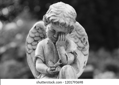 Closeup of putto or child angel sculpture with grieving gesture and butterfly in the hand, black and white image with beautiful bokeh lights, copy space for text, horizontal