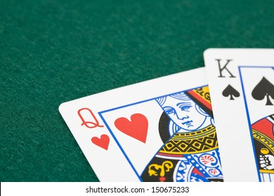 Closeup of queen of hearts and king of spades playing cards over green felt surface
